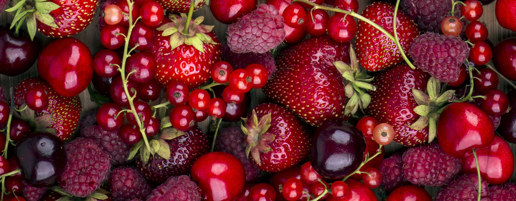 A close-up of fresh red strawberries, cherries, raspberries and huckleberries.