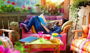 A white woman is curled up on a balcony chair, reading a book and petting a sleepy cat. She is surrounded by brightly-colored flowers and furniture.